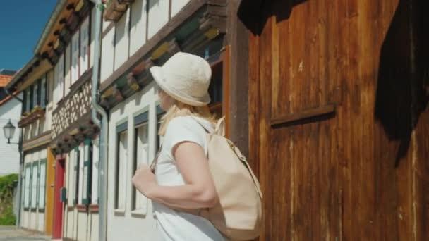 Šťastné turistické žena obdivuje starou ulici malé německé městečko Wernigerode. Turistika v Německu a Evropě koncepce