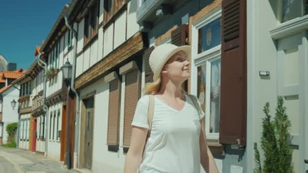 A woman tourist enjoys a walk along the beautiful deserted street of the city of the German city of Wernigerode. She admires the beautiful old houses