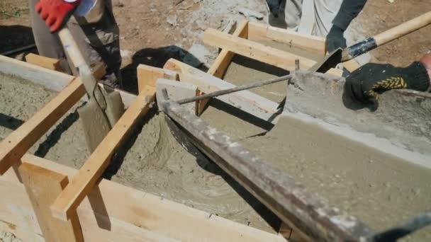 Práce s beton v konstrukci malého domu. Kapaliny betonu do dřevěné bednění, aby spodní části budovy
