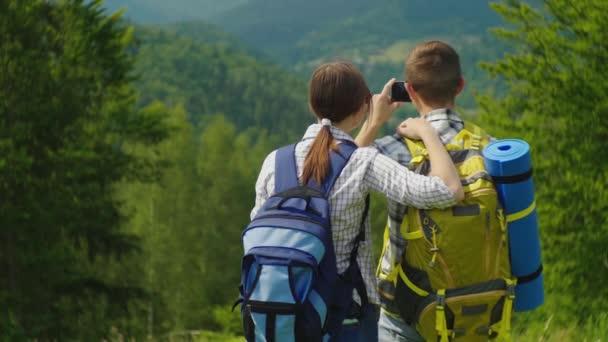 A couple of travelers with backpacks take pictures of a beautiful mountain landscape. Active vacation together