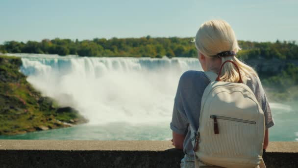 Ein Tourist mit einem Rucksack hinter ihm sieht an den Niagarafällen. Rückansicht, genommen von der kanadischen Küste. Auf dem Bild sehen Sie einen Wasserfall an der amerikanischen Küste