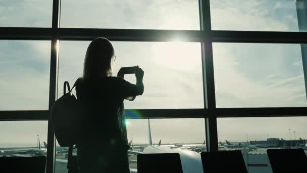 Genießen Sie die Reise. die Frau fotografiert den Flughafen durch ein großes Terminal-Fenster
