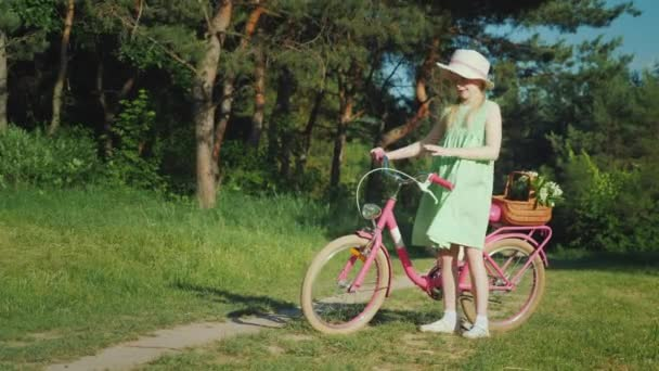 A lány a nyári ruha állandó közelében egy kerékpár, nézi a kamerát. A kosár vadvirágok.