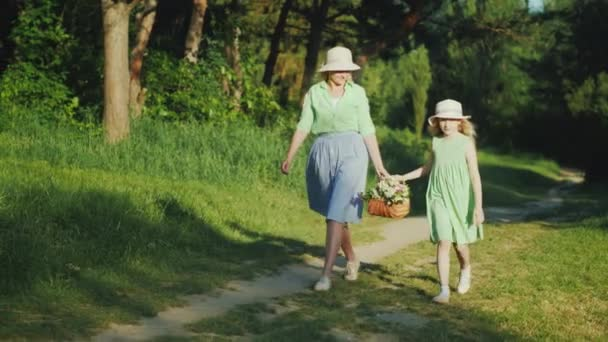 Mom and daughter are walking along a path in the forest, carrying a basket with wildflowers. Happy parents with children