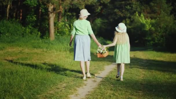 Mom and daughter are walking along a path in the forest, carrying a basket with wildflowers. Happy parents with children. Rear view