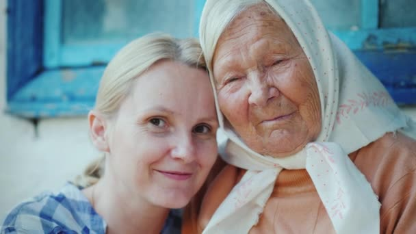 Portrét starší ženy s vnučkou. Berou, dívají se na kameru. Několik generací rodiny