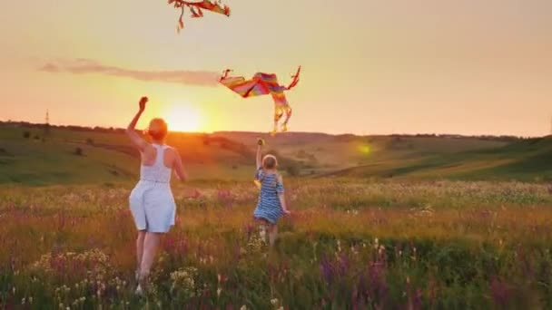 Mom and daughter together launch kites. In a picturesque place at sunset. Happy family concept