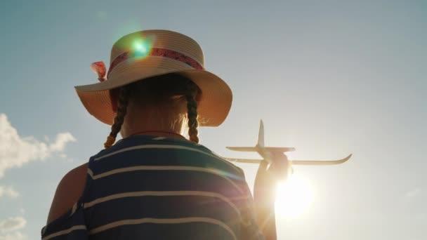 Roztomilé dítě hraje s dětskou pistolku. V paprscích slunce, zadní pohled. Koncept Baby dreams