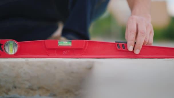 Egy mérnök ellenőrzi az építési pontosság egy vízmérték segítségével. A keret csak kézzel láthatók