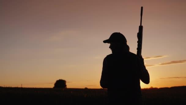 Egy nő, egy fegyverrel megy a mezőn. A vadászati idény elején. Hátulsó nézet