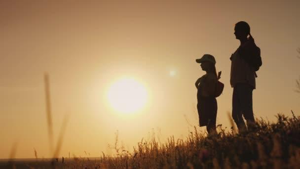 Mamma e figlia sono ammirando il sorgere del sole. Si levano in piedi con gli zaini dietro le spalle in un luogo pittoresco. In viaggio con bambini concetto