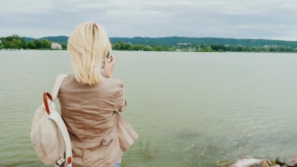 eine Frau fotografiert einen schönen See. zurück
