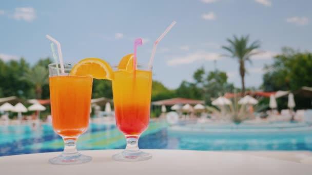 Zwei coole Cocktails stehen auf dem Tisch im Hintergrund des Pools und der Palmen. Paradies und Luxus-Resort