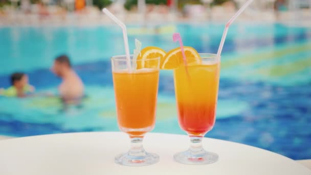 zwei Cocktails mit Strohhalmen auf dem Hintergrund des Pools. der Pool verschwimmt Konturen Vater lehrt seine Tochter schwimmen. Urlaub mit Kindern im Luxus-Resort-Konzept