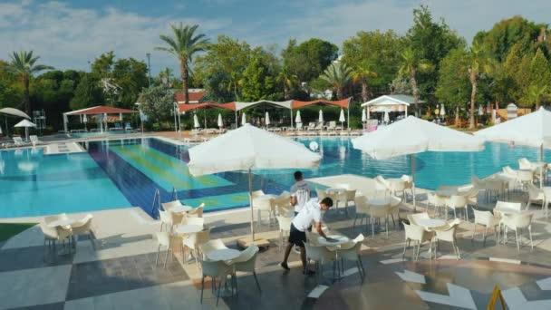 Kemer, Türkei, Juni 2018: Die Mitarbeiter des Hotels entfernt das Gebiet in einem fünf-Sterne-Hotel. Am Pool gibt es Tische und Sonnenschirme - alles ist eine gemütliche Rast in der Türkei