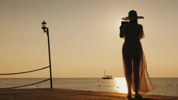 A young woman in beach clothes is standing on the pier and is taking a photo of a beautiful sunrise