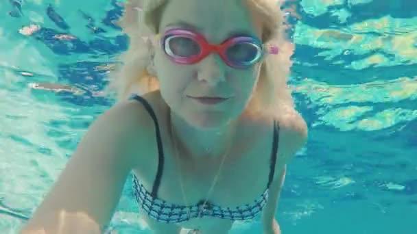 Eine junge Frau erschießt sich in dem Video unter Wasser. schwimmt im Pool, blickt mit Schwimmbrille in die Kamera