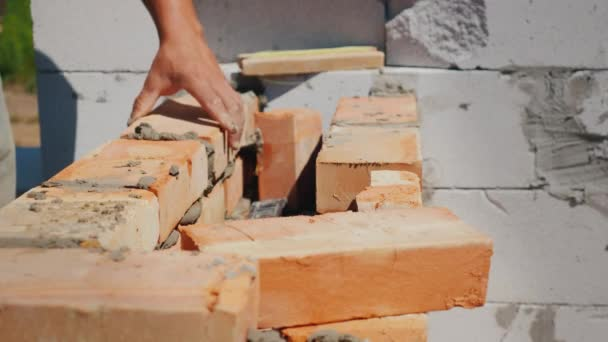 The hands of the worker, makes brick masonry