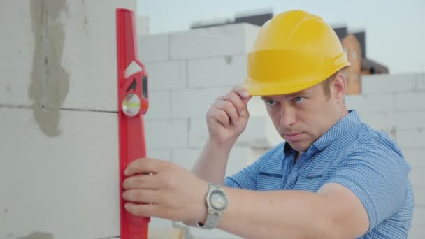 An engineer in a yellow helmet checks the accuracy of the construction work. Quality control at the construction site