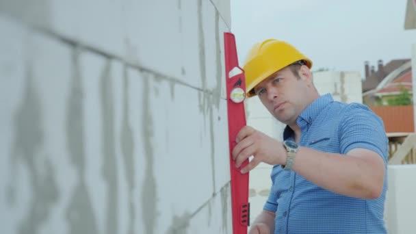 Az építész, a sárga sisak szintű ellenőrzi a falak, a ház építésének pontosságát. Minőség-ellenőrzés, az építkezésen