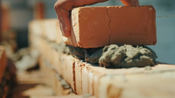 The builders hand puts the brick in the masonry of the wall.