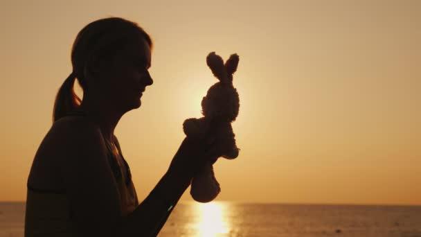 Silhouette spielt eine Frau im Morgengrauen mit einem Spielzeughasen. Kindheitserinnerungen