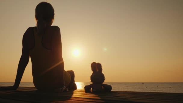 Eine Frau sitzt auf einem Steg neben einem Spielzeughasen. Gemeinsam begegnen sie dem Sonnenaufgang über dem Meer. Romantische Stimmung und Kinderträume