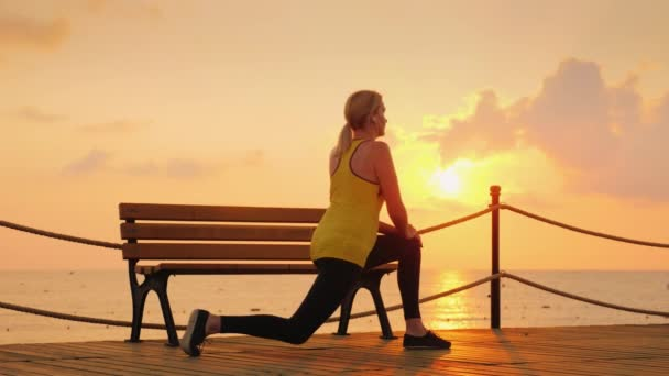 A young athlete makes a morning warm-up on the sea pier of a cool morning against the background of the rising sun