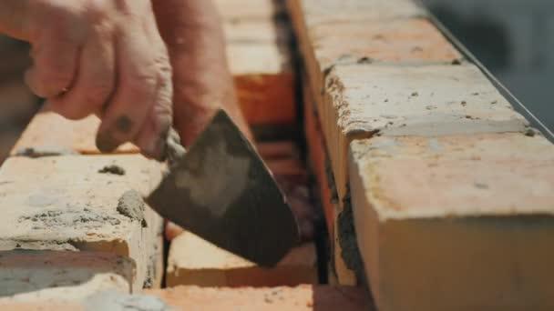 Kvalifikovaný dělník staví cihlu zděné zdi. Manuální práce na staveništi