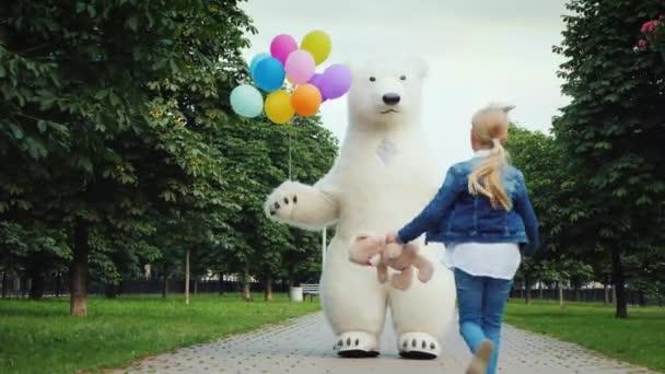 Šťastné dětství. Malá holčička s plavé vlasy běhy plnit velký bílý medvěd, ona má medvídek v jejích rukou. Velký růst panenka