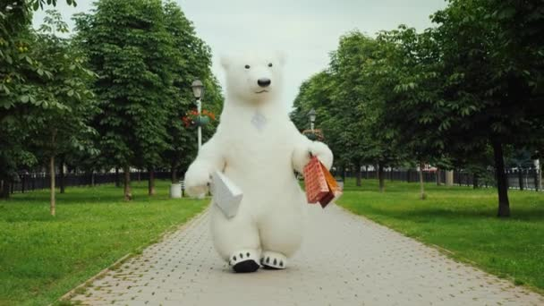 Successful shopping, a polar bear walks in the park with packages for shopping
