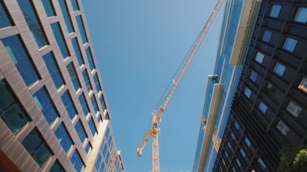 A huge construction crane near office buildings with glass facades. City building. Low angle wide shot
