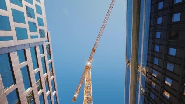 Jít po ulici pod obrovským věžový jeřáb. Výstavba v centru velkých měst. Nízký úhel široký záběr