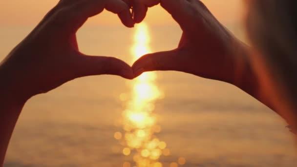 Ženské ruce ukazují tvar srdce nad mořem, kde vychází slunce. Krásná romantická scéna
