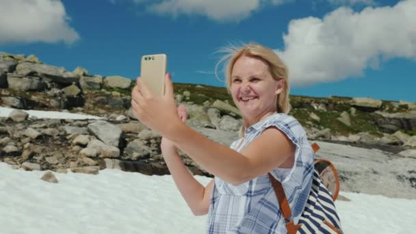 A happy woman doing selfie on a glacier in Norway  Hot weather, but the  snow has not melted yet  The amazing nature of Scandinavia