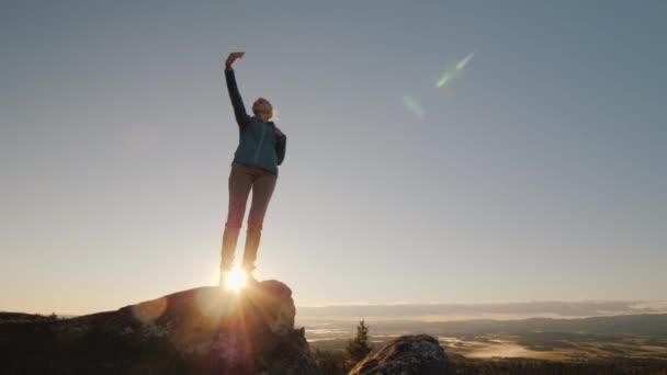eine aktive Frau fotografiert sich auf dem Gipfel eines hohen Berges. im Morgengrauen, steht oben. Erfolgreiches Konzept für aktive Frauen