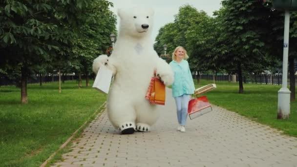 Elegantní dívka je spokojen s osvědčenými nákupy společně se svým přítelem velký medvěd lední, vesele nesou plnou balíčků nákupů