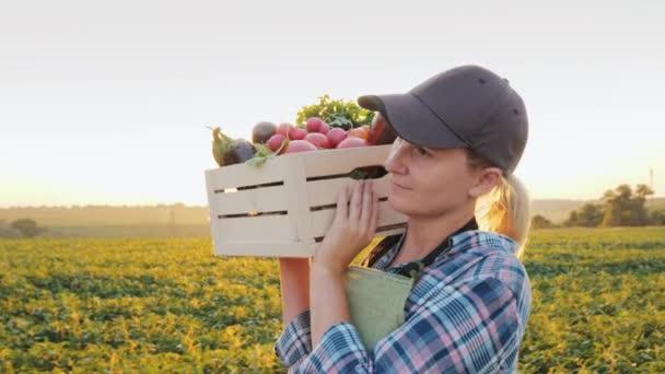 Ženský box čerstvé zeleniny vesničana podél její pole. Zdravé stravování a čerstvá zelenina
