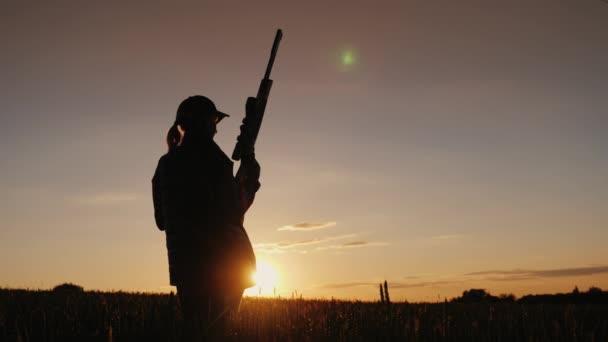 Sziluettjét, egy nő, egy puska. A szitán, a mezőben a naplemente. Sport, fényképezés fogalmát. Hátulnézet