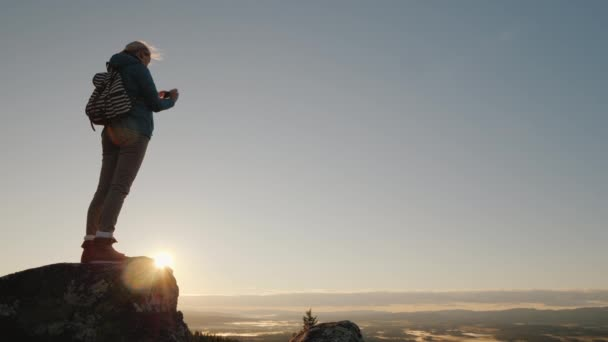 An active woman takes pictures of a beautiful landscape at her feet, standing on top of a mountain. Traveling in Norway