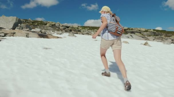 A woman is walking on the snow in the mountains. Outside, its a hot summer, the snow has not melted yet. The amazing nature of Norway
