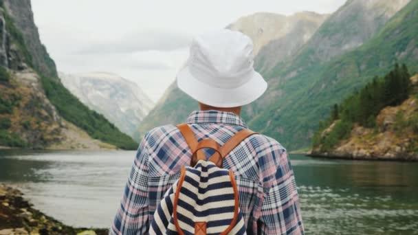A fenséges fjord-ban Norvégia néz egy nő egy hátizsák, háta mögött. Utazás és a turizmus koncepcióban Scandinavia