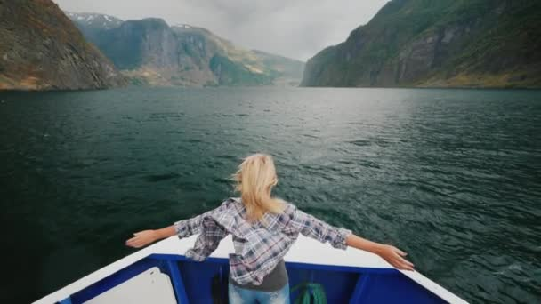 A woman is standing on the bow of the ship sailing over the fjord in Norway. Enjoys the journey, the wind waves her hair