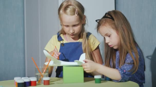 Two children together paint the model of the aircraft. Developmental games for children