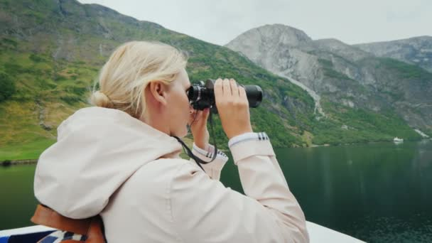 Egy nő áll az íj, a hajó belenéz a távcsövet. Hajókázás a norvég fjordok