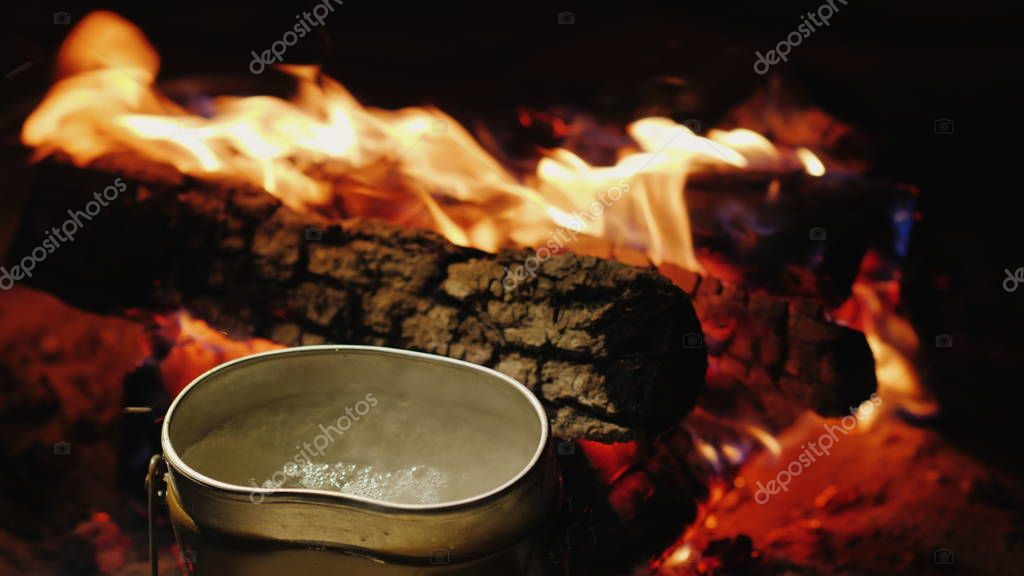 The camp kettle is boiling around the fire. Preparation of hot tea and food on a hike