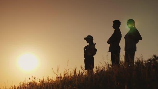 Genitori con il bambino sono ammirando il tramonto. Escursione con bambini concetto
