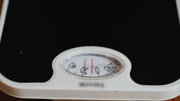 Close-up video: A man measures his weight on a mechanical floor scales.