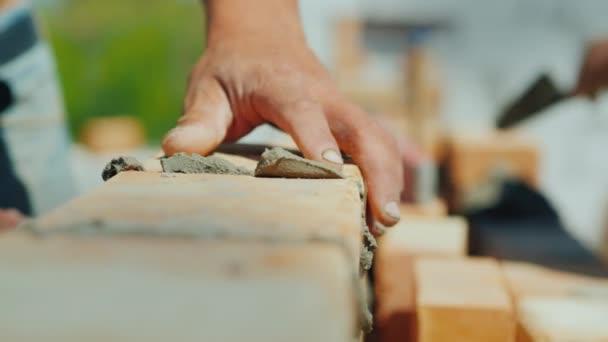 Dva specialista stavitelé postavit dům z cihel, detail rukou s cihlou