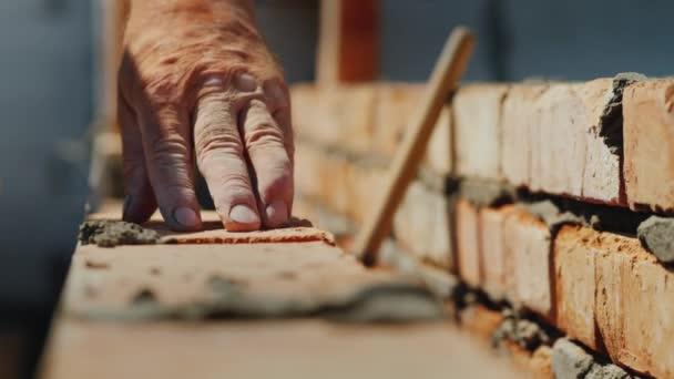 Výstavba nového bytového domu s jejich vlastních rukou, cihelného zdiva starší muž, detail